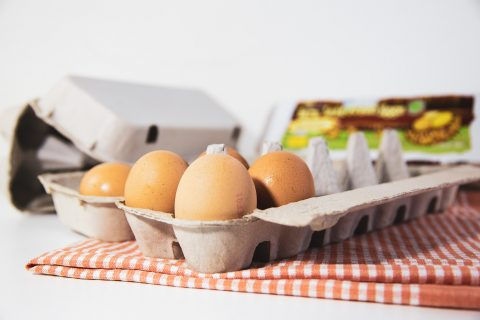 Carton Packaging egg carton open with eggs more cartons in the back ground